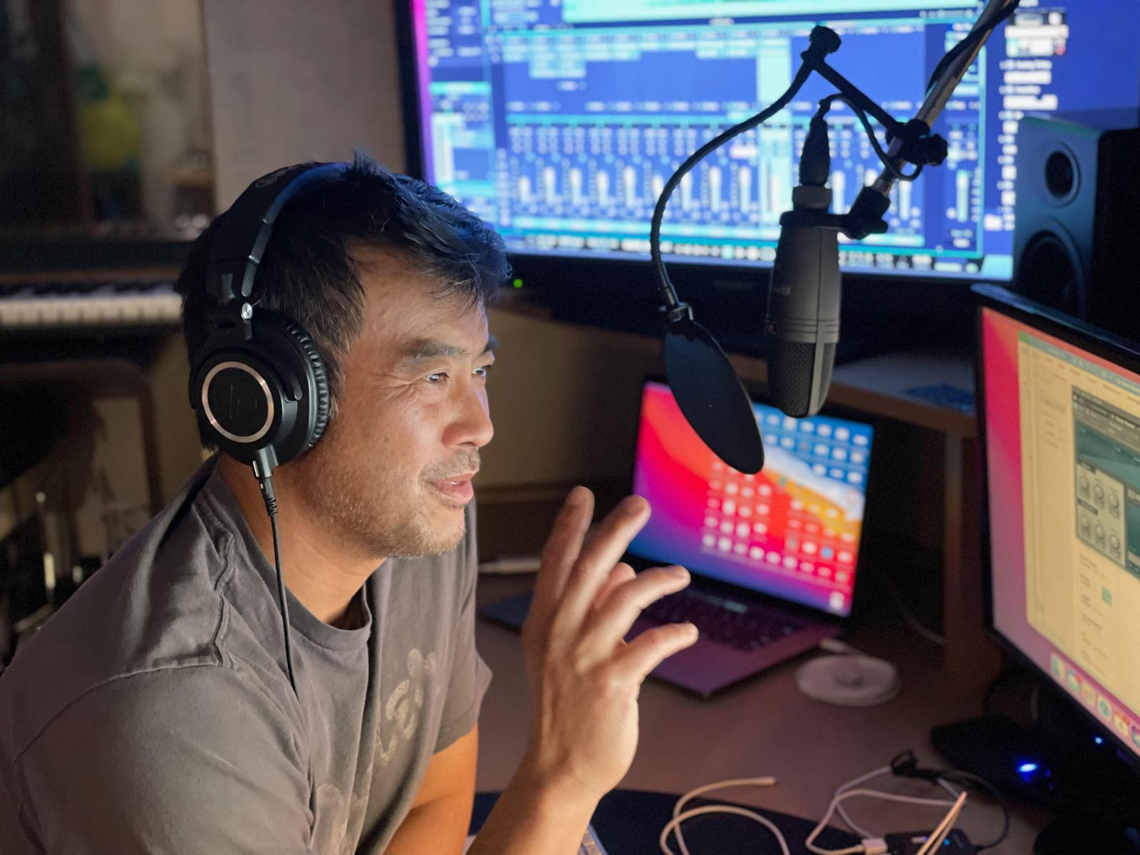 podcast host Jeff Yasuda speaking into a microphone in a recording studio